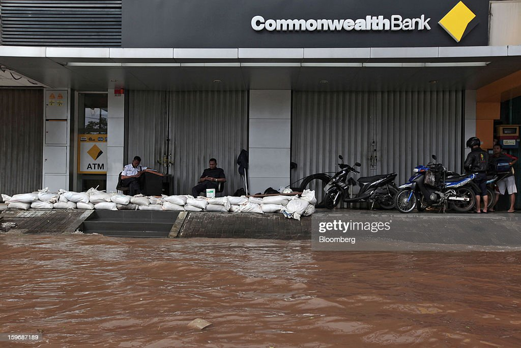 Security guards sit behind sandbags outside a shuttered Commonwealth Bank of Australia branch in Jakarta, Indonesia, on Friday, Jan. 18, 2013. Indonesia declared a state of emergency in Jakarta as flooding brought traffic to a standstill in the city of 9.6 million people and swamped the offices of President Susilo Bambang Yudhoyono. Photographer: Dimas Ardian/Bloomberg via Getty Images