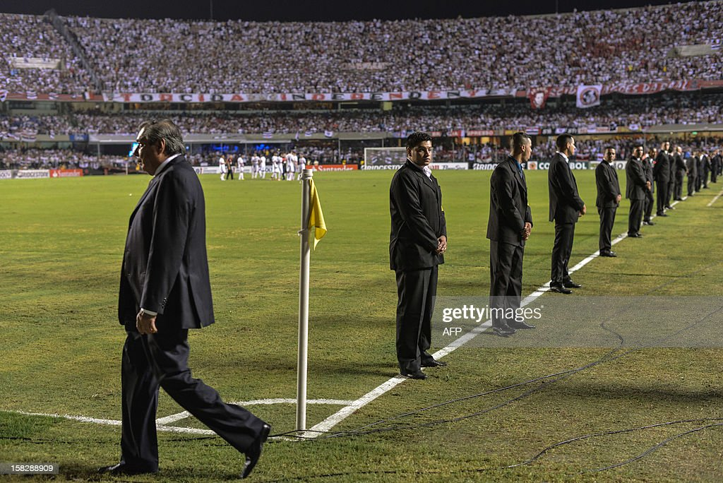 Security guards stand along the side line as Brazil's Sao Paulo waits for Argentine's Tigre during their Copa Sudamericana football final match against at Morumbi stadium in Sao Paulo, Brazil, on December 12, 2012. Tigre's players didn't show up for the second half and Sao Paulo won by 2-0. AFP Photo/Yasuyoshi CHIBA