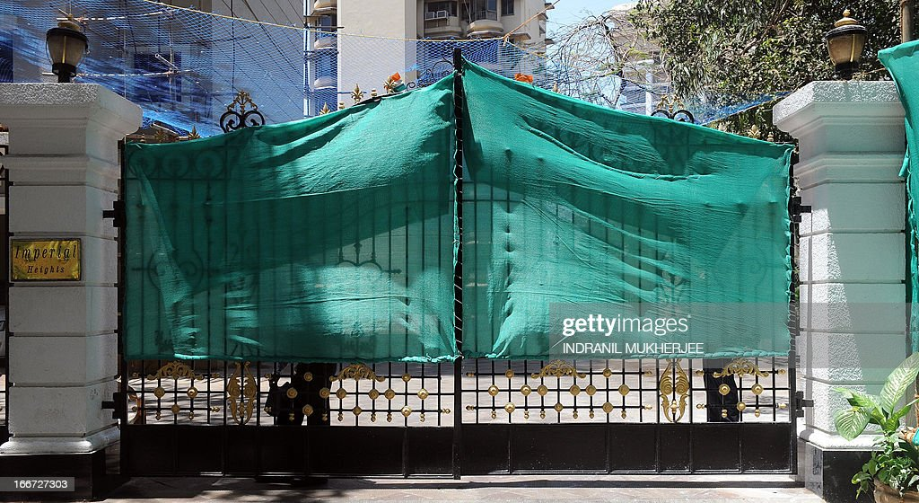 Security guards stand behind green shrouds obsucring the entrance gate to the residence of Indian Bollywood actor Sanjay Dutt in Mumbai on April 16, 2013. Bollywood star Sanjay Dutt has asked India's top court for more time before going back to jail for possessing arms supplied by plotters of the deadly 1993 Mumbai blasts, his lawyer said April 16. India's Supreme Court last month struck down Dutt's appeal over his conviction and said he must return to prison by April 18, but the 53-year-old has asked for another six months of freedom to complete his filming obligations. AFP PHOTO/ INDRANIL MUKHERJEE