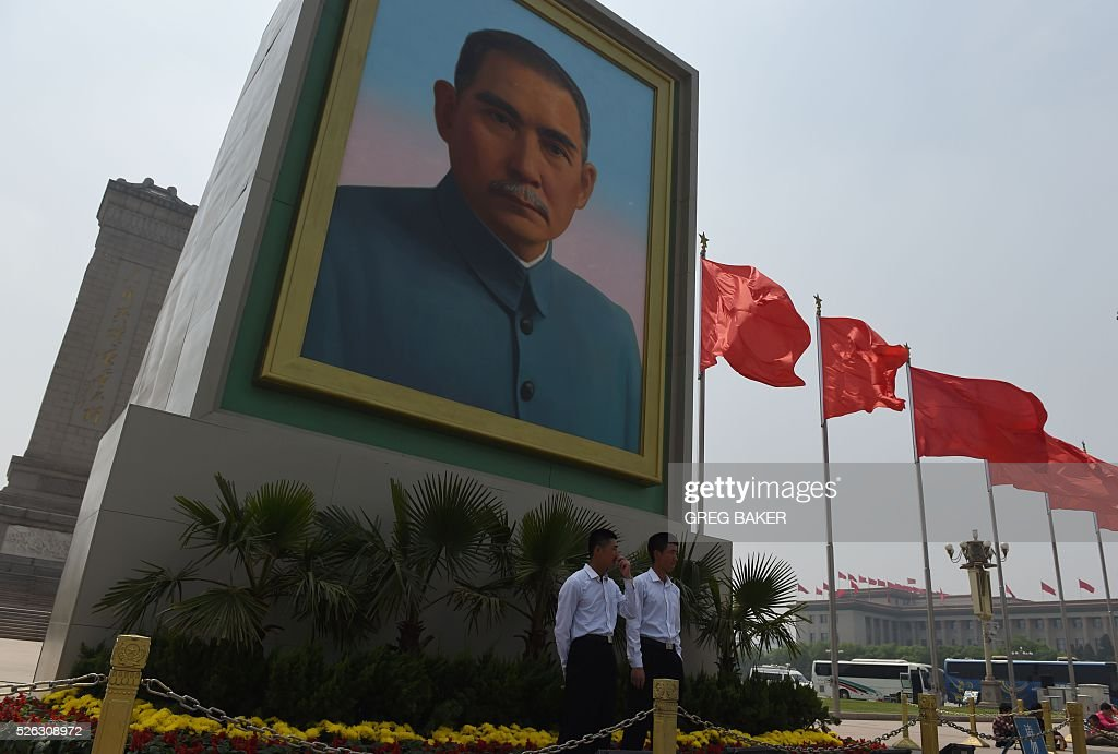 Security guards stand below a portrait of Sun Yat-sen in Beijing's Tiananmen Square on the eve of May Day on April 30, 2016. Sun is considered the founding father of modern China after his 1911 overthrow of imperial rule by the Qing Dynasty. / AFP / GREG