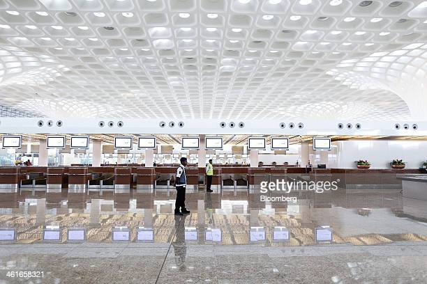 Security guards stand inside the newly built Terminal 2 of the Chhatrapati Shivaji International Airport operated by GVK Power Infrastructure Ltd in...