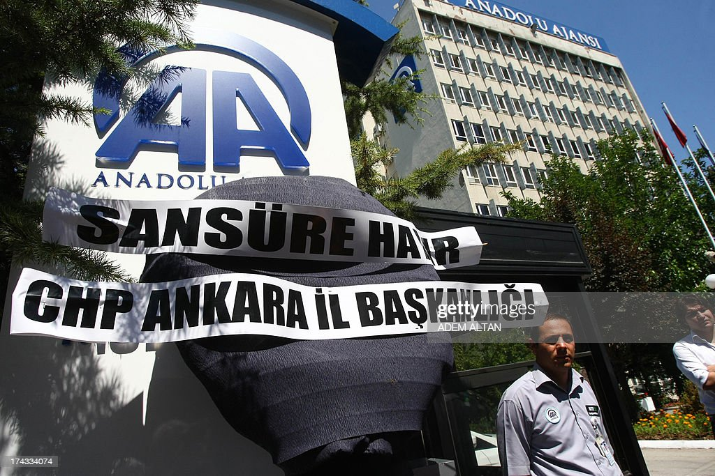 Security guards stand on July 24, 2013 outside the headquarters of the Anadolu Agency in Ankara as a group of journalists and members of the Republican People's Party, CHP, protest against censorship in Turkish media on Journalism Day.