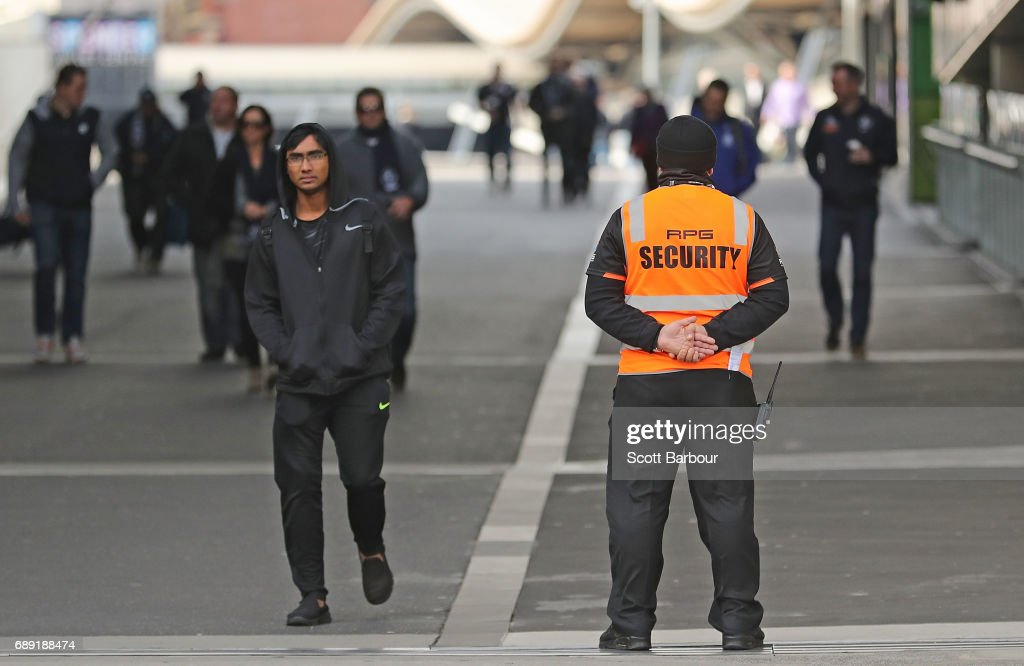 Security guards stand on patrol as football fans walk from Southern Cross Station to the ground during the round 10 AFL match between the Carlton Blues and the North Melbourne Kangaroos at Etihad Stadium on May 28, 2017 in Melbourne, Australia.