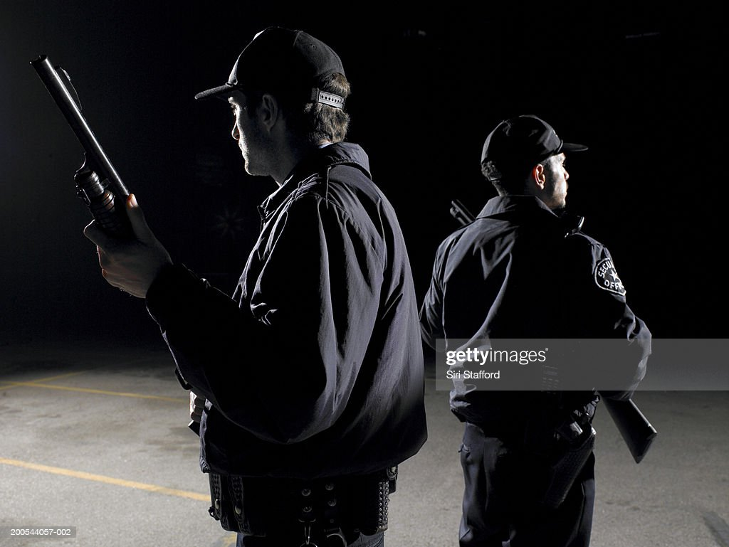 Security guards standing back to back with shotguns : Stock Photo