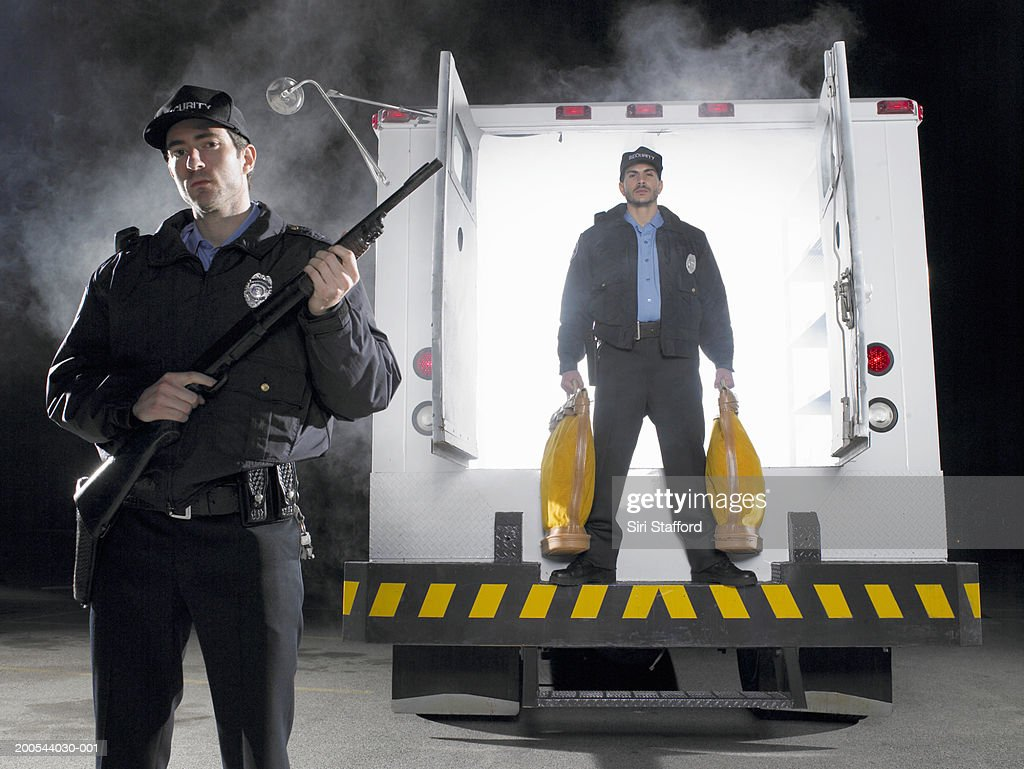 Security guards standing in back of armored truck, one with money bags