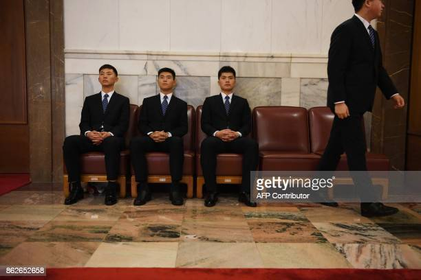 Security guards wait in the Great Hall of the People as Chinese President Xi Jinping speaks during the opening ceremony of the 19th Communist Party...