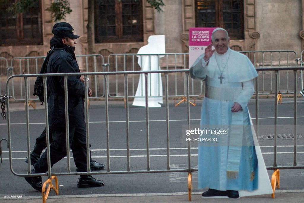 Security guards walk near an image of Pope Francis, in Mexico City on February 12, 2016 hours before the arrival of the pontiff to the country. Pope Francis left Rome on Friday bound for Cuba, where he is to hold a historic meeting Russian Patriarch Kirill before continuing on to Mexico for a five-day visit. AFP PHOTO / Pedro PARDO / AFP / Pedro PARDO