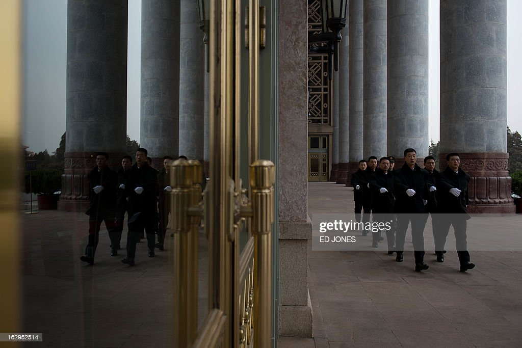 Security guards walk outside the Great Hall of the People during a meeting of the Chinese People's Political Consultative Conference (CPPCC) on March 2, 2013. China will convene a key legislative session, with new Communist Party chief Xi Jingping set to become president during the two-week meeting. AFP PHOTO / Ed Jones