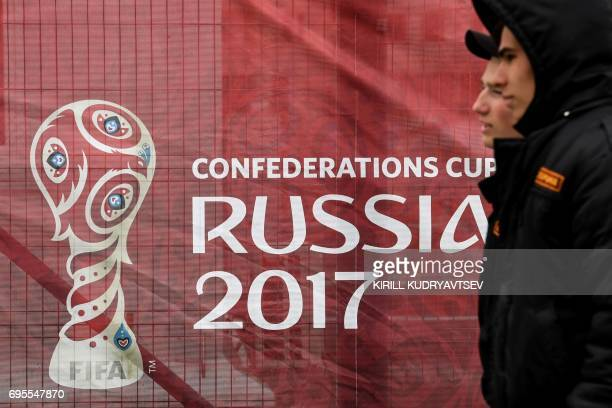 TOPSHOT Security guards walk past a banner of 2017 FIFA Confederations Cup football tournament outside the Otrkytie Arena in Moscow on June 13 2017 /...