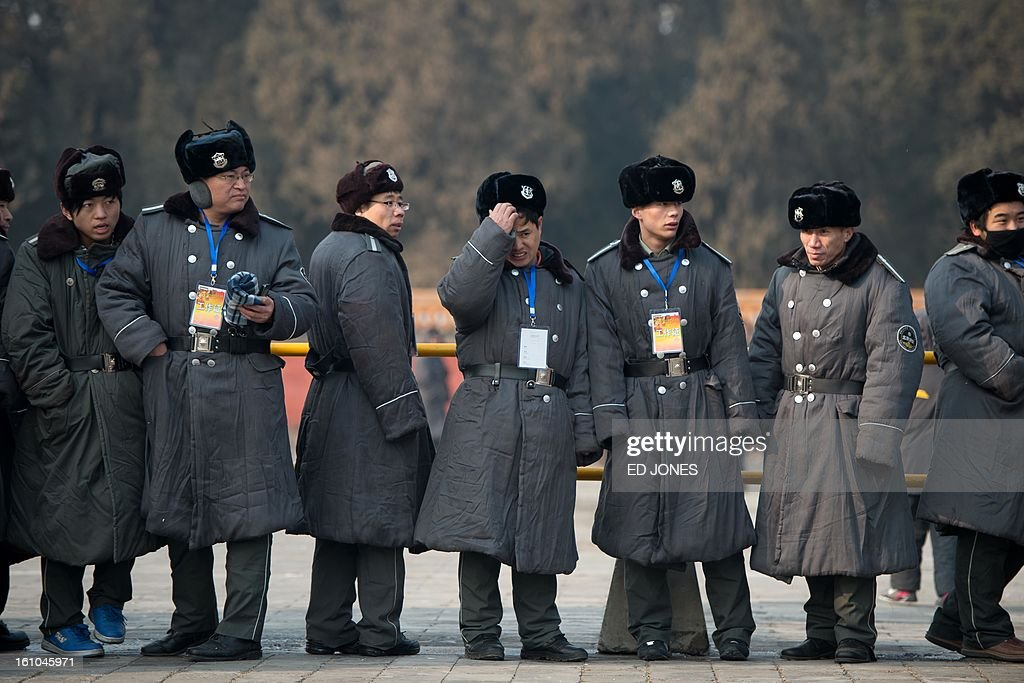 Security guards watch as performers (not pictured) take part in a traditional Qing Dynasty ceremony in which emperors prayed for good fortune, during the opening of an annual fair at the Temple of Earth park in Beijing on February 9, 2013, a day before the Lunar New Year. China is preparing to welcome the lunar new year of the snake which falls on Febraury 10. AFP PHOTO / Ed Jones
