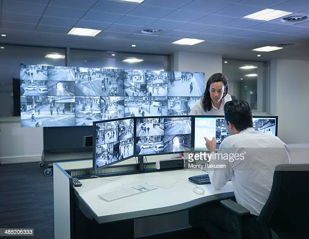 Security guards working at CCTV screens in control room