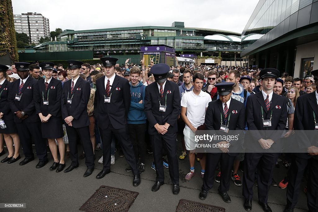 Security hold back spectators as they queue to enter The All England Lawn Tennis Club in Wimbledon, southwest London, on June 27, 2016 on the first day of the 2016 Wimbledon Championships. / AFP / ADRIAN