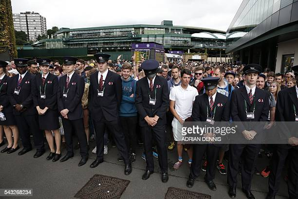 Security hold back spectators as they queue to enter The All England Lawn Tennis Club in Wimbledon southwest London on June 27 2016 on the first day...