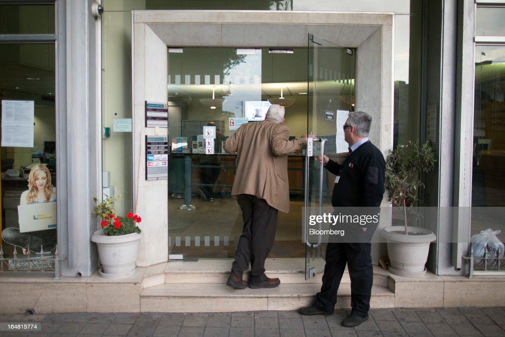 A G4S security holds a door open for an elderly man to enter a Bank of Cyprus Plc branch. as banks open for the first time in two weeks in Nicosia, Cyprus, on Thursday, March 28, 2013. The Central Bank of Cyprus's capital controls will include a 300-euro ($383) daily limit on withdrawals and restrictions on transfers to accounts outside the country. Photographer: Simon Dawson/Bloomberg via Getty Images