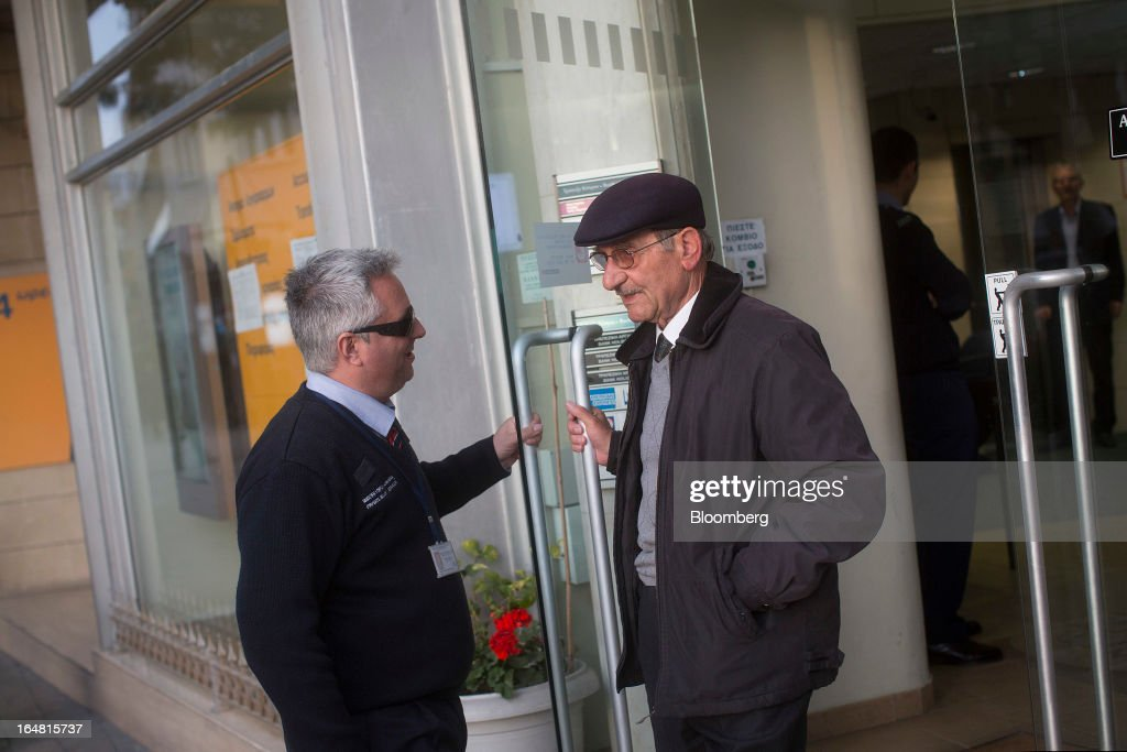 A G4S security holds a door open for customers as they exit a Bank of Cyprus Plc branch. as banks open for the first time in two weeks in Nicosia, Cyprus, on Thursday, March 28, 2013. The Central Bank of Cyprus's capital controls will include a 300-euro ($383) daily limit on withdrawals and restrictions on transfers to accounts outside the country. Photographer: Simon Dawson/Bloomberg via Getty Images