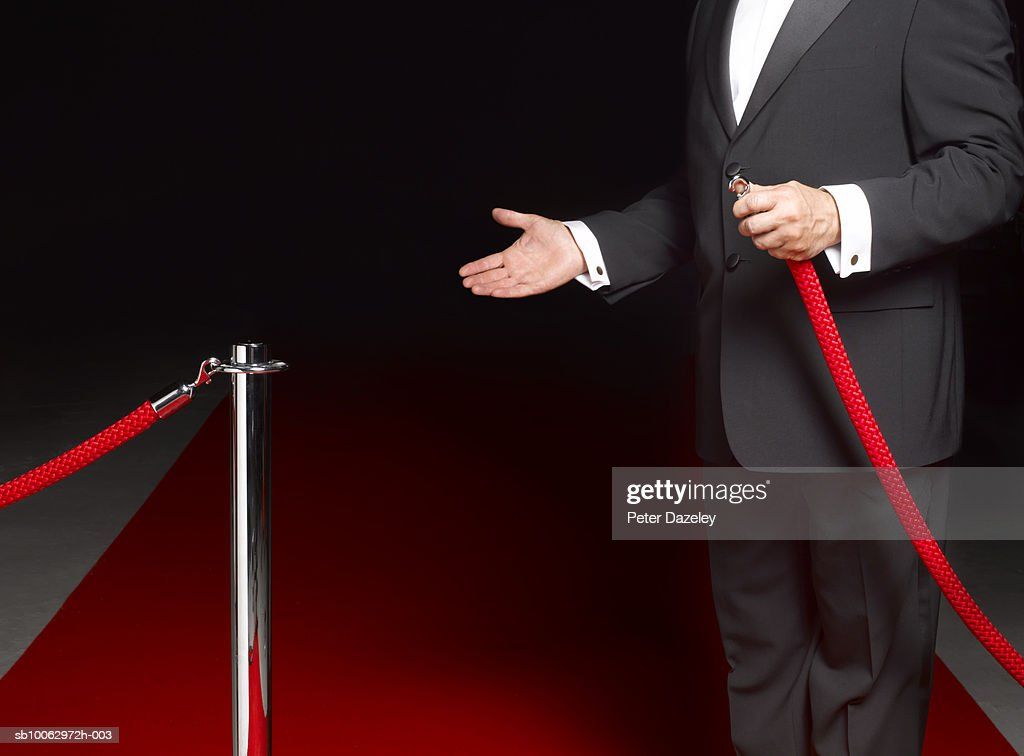 Security man showing way past rope on to red carpet, mid section : Stock Photo
