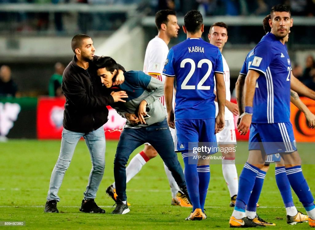A security man stops a man who tried to take a selfie during the Russia 2018 FIFA World Cup European Group G qualifying football match between Israel and Spain at Teddy Stadium in Jerusalem on October 9, 2017 Spain is already qualified for the 2018 World Cup in Russia. /