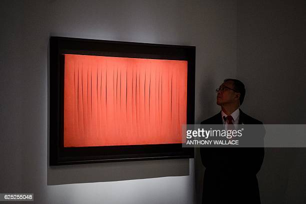 A security member looks at Lucio Fontana's 'Concetto Spaziale Attese at 'The Loaded Brush' display by auction house Christie's in Hong Kong on...
