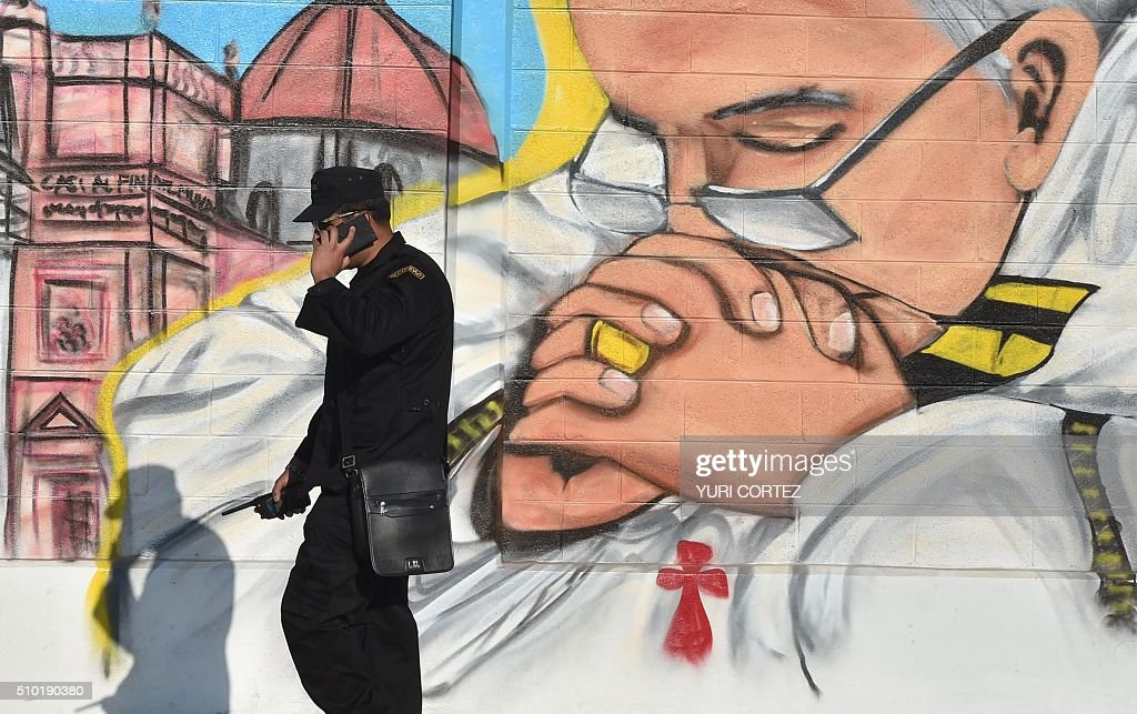 A security member speaks on his mobile phone next to a mural painting depicting Pope Francis in Ecatepec --a rough, crime-plagued Mexico City suburb-- where the latter is to celebrate an open-air mass, on February 14, 2016. Pope Francis has chosen to visit some of Mexico's most troubled regions during his five-day trip to the world's second most populous Catholic country. AFP PHOTO / YURI CORTEZ / AFP / YURI CORTEZ