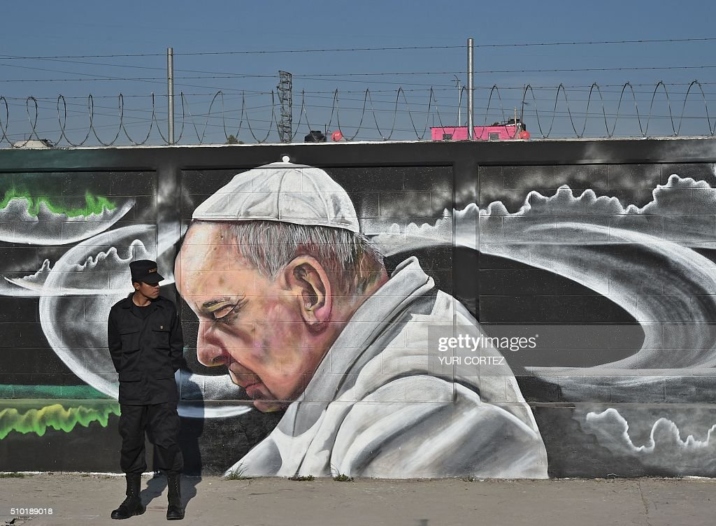 A security member stands guard next to a graffiti depicting Pope Francis in Ecatepec --a rough, crime-plagued Mexico City suburb-- where he will celebrate an open-air mass, on February 14, 2016. Pope Francis has chosen to visit some of Mexico's most troubled regions during his five-day trip to the world's second most populous Catholic country. AFP PHOTO / YURI CORTEZ / AFP / YURI CORTEZ