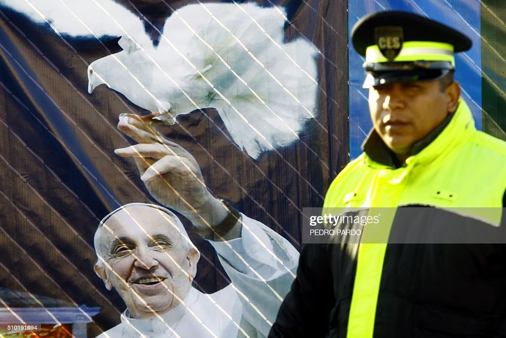 A security member walks by a poster of Pope Francis in Ecatepec --a rough, crime-plagued Mexico City suburb-- where he is to celebrate an open-air mass, on February 14, 2016. Pope Francis has chosen to visit some of Mexico's most troubled regions during his five-day trip to the world's second most populous Catholic country. AFP PHOTO / PEDRO PARDO / AFP / Pedro PARDO
