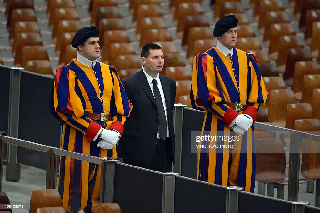 A security mmber is flanked by Swiss Guards prior the pontif's weekly general audience on January 9, 2013 at the Paul VI hall at the Vatican.