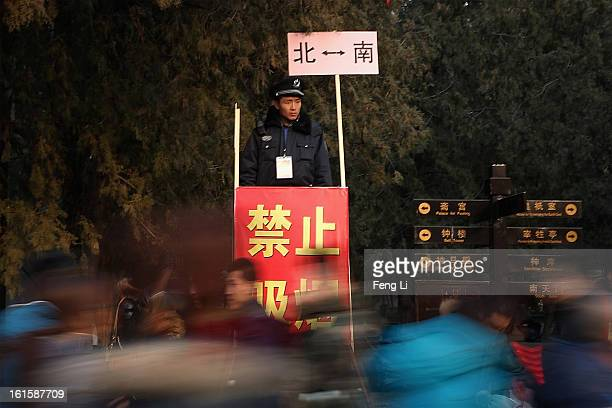 A security officer guards on the top of a ladder during the Spring Festival Temple Fair at the Temple of Earth park on February 12 2013 in Beijing...