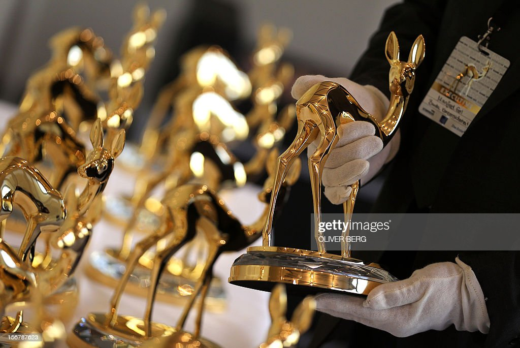 A security officer inspects Bambi trophies in Duesseldorf, western Germany, on November 21, 2012. The Bambis are the main German media awards and will be presented on November 22, 2012. AFP PHOTO / OLIVER BERG GERMANY OUT
