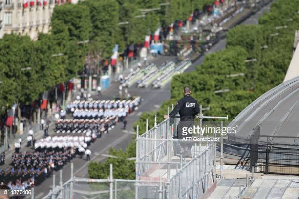 A security officer is seen on a roof top overlooking the ChampsElysees during the annual Bastille Day parade in French capital Paris on July 14 2017...