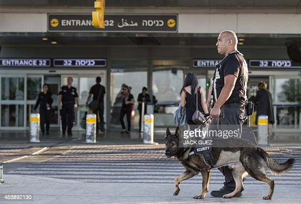 A security officer leads a dog as they patrol the entrance of Ben Gurion International airport near the Mediterranean Israeli coastal city of Tel...