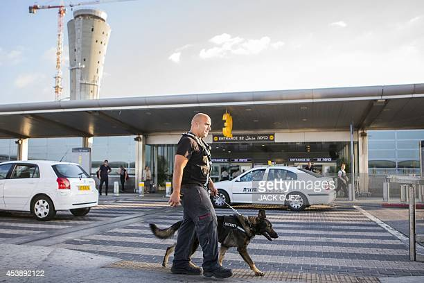 A security officer leads a dog as they patrol the entrance to passangers terminal of Ben Gurion International airport near the Mediterranean Israeli...
