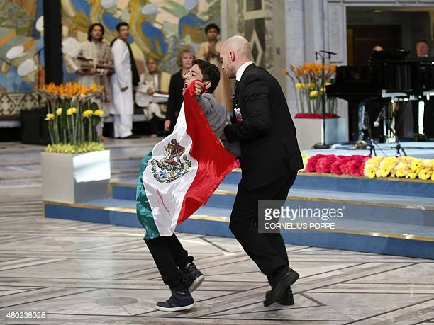 A security officer leads away a man displaying a flag of Mexico during the Nobel Peace Prize awards ceremony at the City Hall in Oslo Norway on...