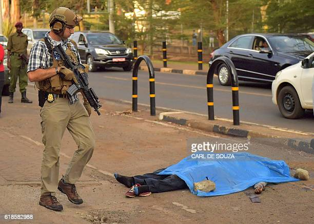A US security officer looks at the body of an assailant after he was shot and killed by Kenyan police outside the US embassy in the capital Nairobi...