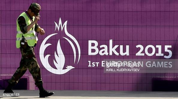 A security officer passes a banner announcing the 2015 European Games in front of the Athletes village in Baku on June 10 2015 AFP PHOTO / KIRILL...