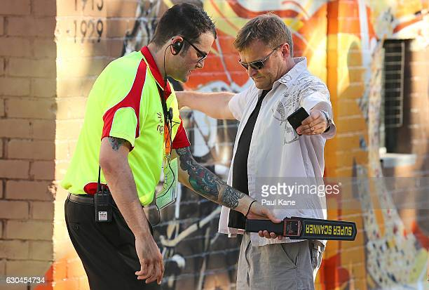 A security officer runs a metal detector over a spectator before entry to the ground during the Big Bash League between the Perth Scorchers and...