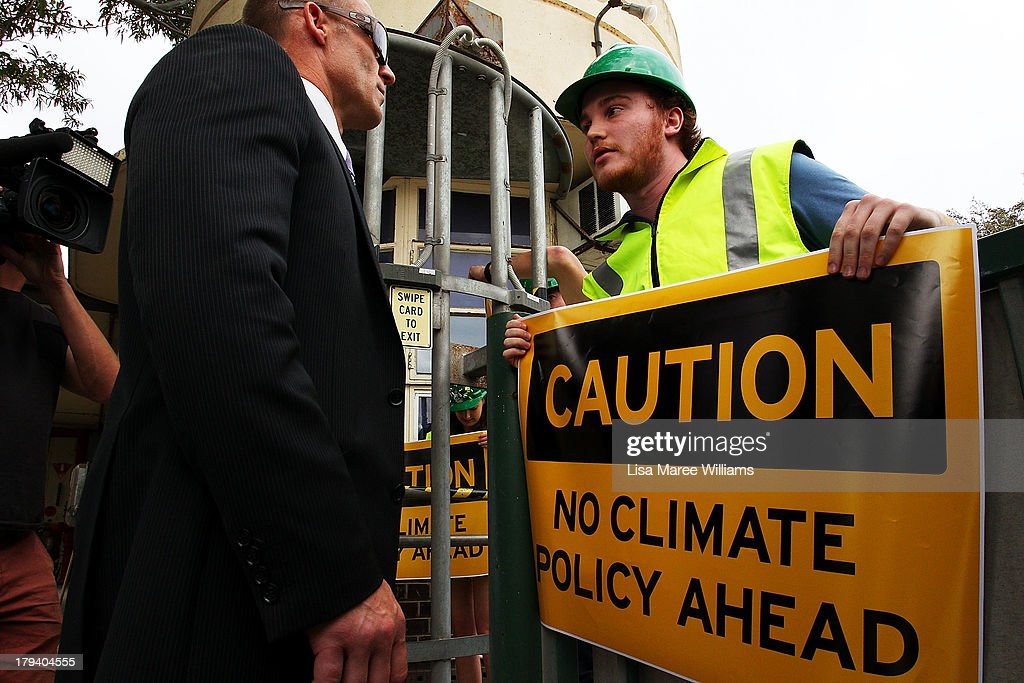 A security officer speaks with a protester as he waits for Australian Opposition Leader, Tony Abbott at Penrice Soda factory on September 3, 2013 in Adelaide, Australia. In the 2010 election the Australian Labor Party recorded its highest two-party-preferred vote since 1969 in South Australia, but if nationwide polling proves accurate the Liberal-National Party coalition believe they can gain seats in the state.