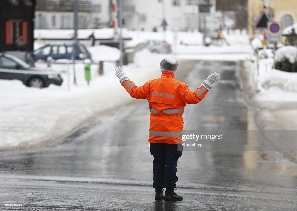 A security officer stands and directs traffic through the streets of Davos, Switzerland, on Monday, Jan. 21, 2013. This week the business elite gathers in the Swiss Alps for the 43rd annual meeting of the World Economic Forum in Davos, the five day event runs from Jan. 23-27. Photographer: Simon Dawson/Bloomberg via Getty Images
