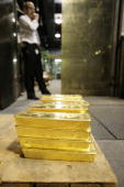 A security officer stands behind 125 kg gold bars on April 6 2009 at a plant of gold refiner and bar manufacturer ArgorHeraeus SA in Mendrisio...