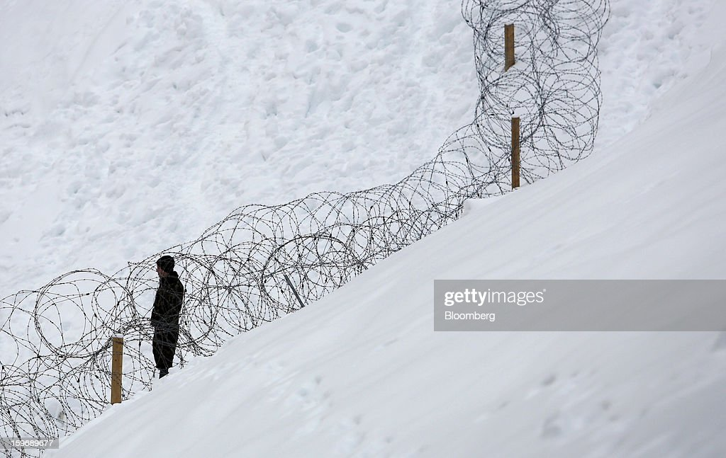 A security officer stands next to a barbed wire fence on the perimeter of the town of Davos in Switzerland, on Thursday, Jan. 17, 2013. Next week the business elite gather in the Swiss Alps for the 43rd annual meeting of the World Economic Forum in Davos, the five day event runs from Jan. 23-27. Photographer: Chris Ratcliffe/Bloomberg via Getty Images