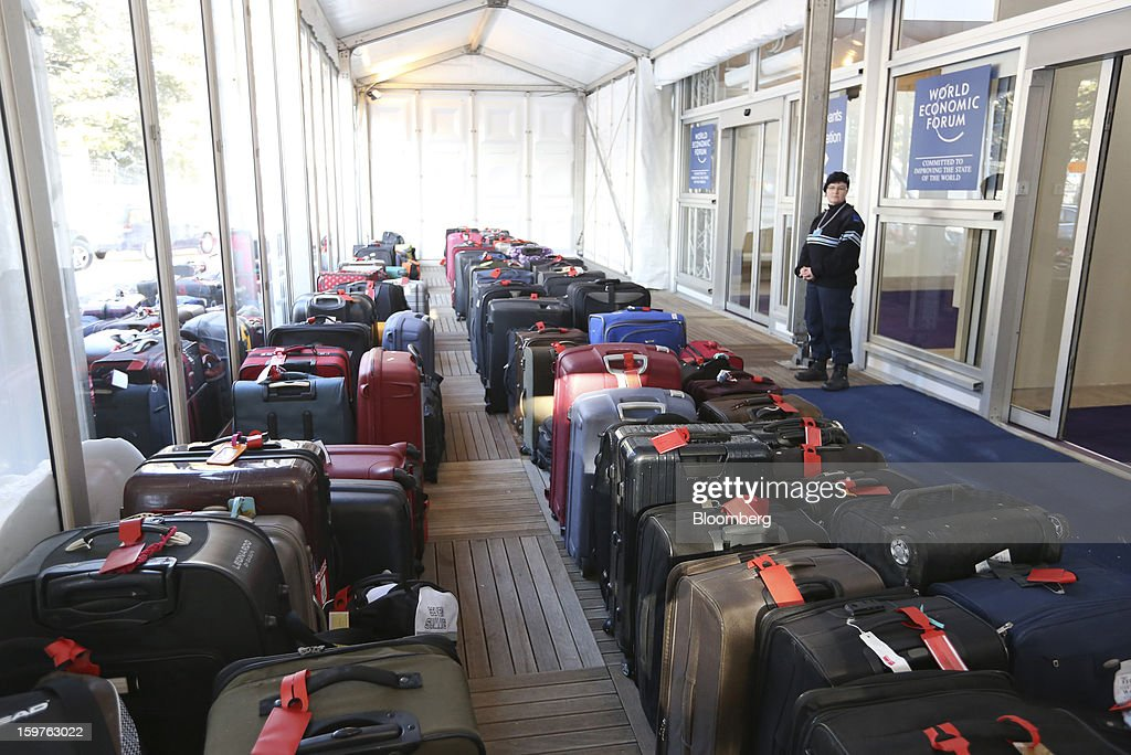 A security officer stands watch over suitcases and baggage dropped at the entrance to the the World Economic Forum media centre in the town of Davos, Switzerland, on Saturday, Jan. 19, 2013. Next week the business elite gather in the Swiss Alps for the 43rd annual meeting of the World Economic Forum in Davos, the five day event runs from Jan. 23-27. Photographer: Chris Ratcliffe/Bloomberg via Getty Images