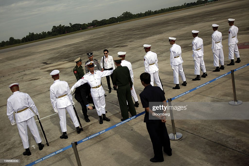A U.S. security officer, third left in black, screens a member of the Burmese military prior to the arrival of U.S. President Barack Obama at Yangon International Airport in Yangon, Myanmar, on Monday, Nov. 19, 2012. Obama hailed Myanmar's shift to democracy and urged more steps to increase freedom in the first visit to the former military regime by a U.S. president. Photographer: Dario Pignatelli/Bloomberg via Getty Images