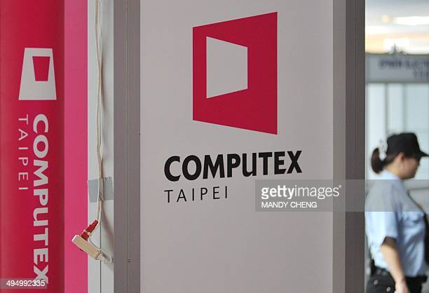 A security officer walks past a billboard featuring Computex Asia's leading IT trade fair in the venue in Taipei on June 1 2014 Asia's largest tech...
