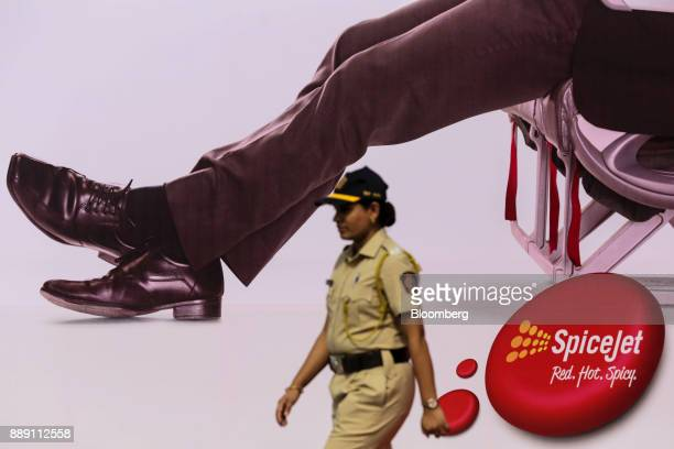 A security officer walks past an advertisement for SpiceJet Ltd during an event in Mumbai India on Saturday Dec 9 2017 SpiceJet an Indian budget...