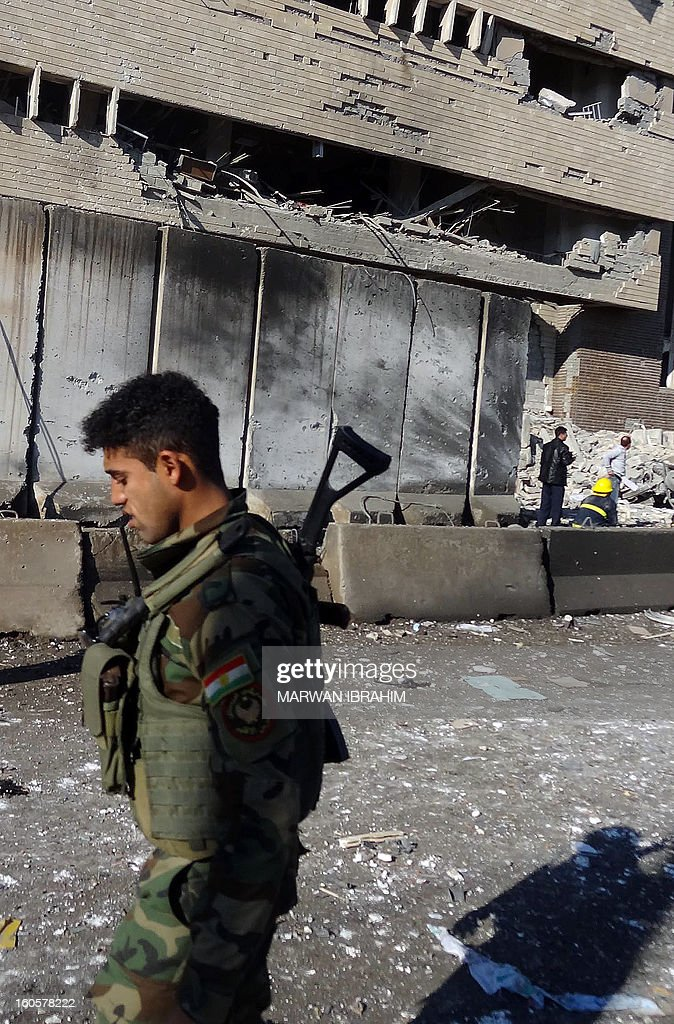A security officer walks past the scene after a car bombing followed by an assault by grenade-throwing gunmen on a police headquarters in a disputed northern city of Kirkuk, on February 3, 2013, killing some 30 people. The vehicle that was detonated in the center of the city was painted to appear as though it was a police car, and the militants who sought to seize the compound were dressed as policemen, witnesses said.