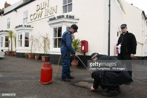 Security officers check the drains outside The Dunn Cow Inn Sedgefield amid speculation British Prime Minister Tony Blair and President Bush may take...