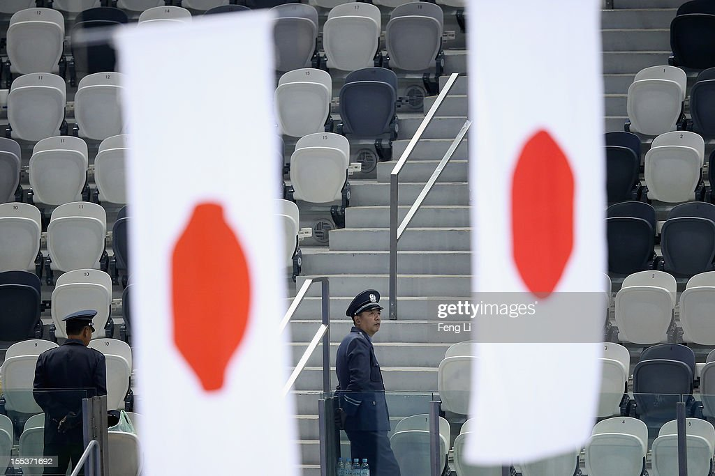 Security officers guard as two Japanese national flags rising during the Men medal ceremony of Cup of China ISU Grand Prix of Figure Skating 2012 at the Oriental Sports Center on November 3, 2012 in Shanghai, China.