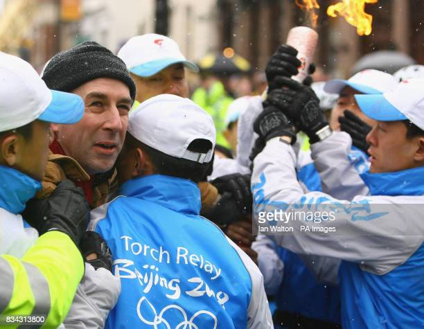 Security officers intervene as a demonstrator grabs and attempts to take the Olympic Torch from British TV presenter Konnie Huq during the relay of...