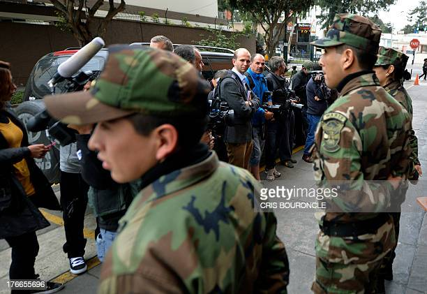 Security officers keep media at bay outside the headquarters of the Peruvian Drug Enforcement Division in Lima on August 16 2013 where Irish...