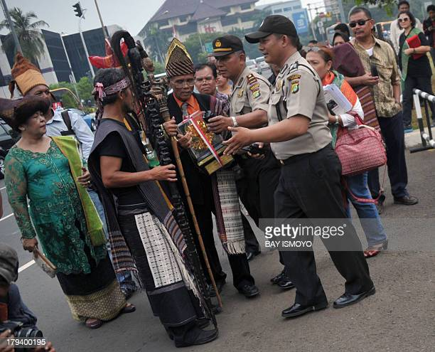 Security officers stand by as 2005 Kalpataru environmental award winners from North Sumatra prepare to place their trophies in front of the...