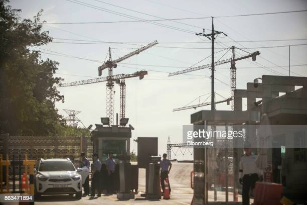 Security officers stand guard at the entrance to the temporarily suspended construction site of ShinKori No 5 and 6 nuclear power reactors owned by...